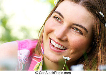 Beautiful young caucasian woman smiling with flower