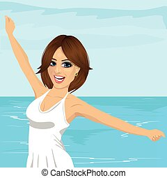 beautiful young caucasian woman with her hands raised at beach