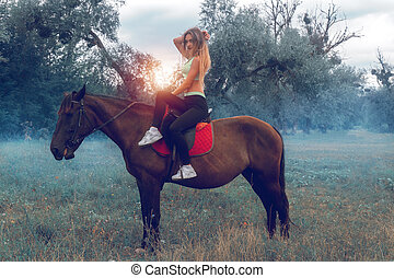 beautiful young circus rider posing on a horse and stares