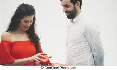Beautiful young couple at home. Hugging Kiss and enjoy time together. Celebration of Valentine's Day. Gift box in hand and balloon in the form of a heart.