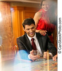 Beautiful young couple behind roulette table in a casino