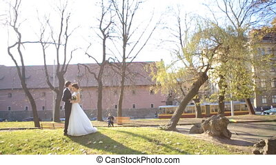 beautiful young couple bride and groom standing in the park at sunset shot in slow motion  close up