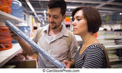 Beautiful young couple choosing boxes and containers in shop