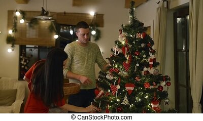 Beautiful young couple decorating Christmas tree at home. -...