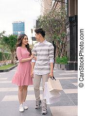 Beautiful young couple enjoying in shopping, having fun together. Consumerism, love, dating, lifestyle concept