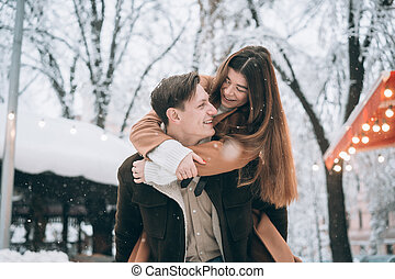beautiful young couple having fun on a snowy street