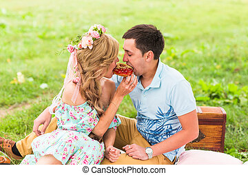 Beautiful Young Couple Having Picnic in Countryside. Happy Family Outdoor. Smiling Man and Woman relaxing in Park. Relationships.
