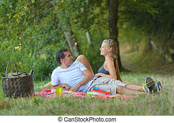 beautiful young couple having picnic in countryside