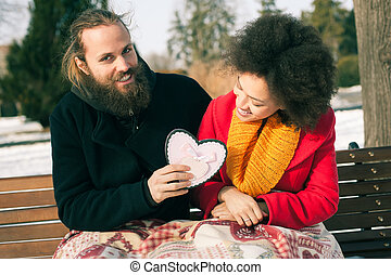 Beautiful young couple holding a big heart in winter day