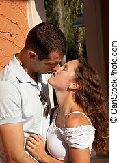beautiful young couple holding each other about to kiss