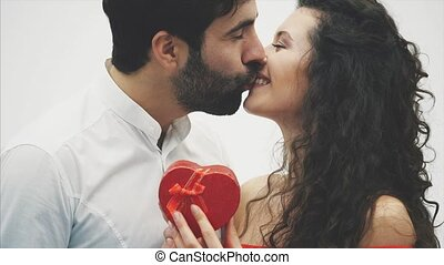 Beautiful young couple. Hugging a kiss and enjoying it together. Valentine's Day Celebration. The guy gives the gift box to the girl in a red dress. Kiss. White background