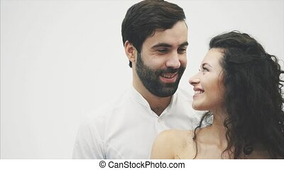 Beautiful young couple. Hugging a kiss and enjoying it together. Valentine's Day Celebration. The guy gives the gift box to the girl in a red dress.