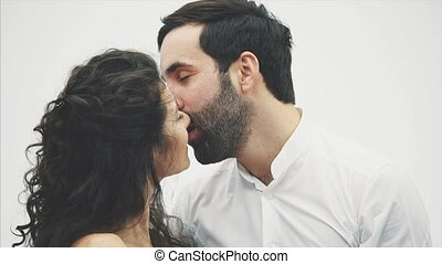 Beautiful young couple . Hugging kissing and enjoying time together. Valentine's Day Celebration. Together raise the gift box up. The girl is dressed in a red dress and her husband in a white shirt