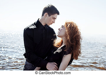beautiful young couple hugging standing in the sea, photo colorization effects