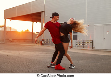 Beautiful young couple in fashionable clothes with a cap dancing at sunset on the street.