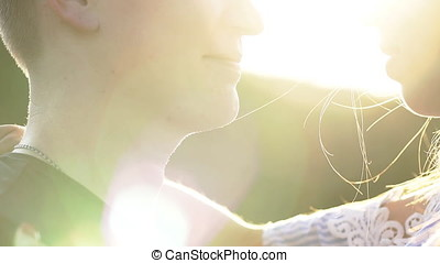 Beautiful Young Couple in Love kiss in a field at sunset