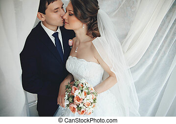beautiful young couple in love kissing under the wedding veil