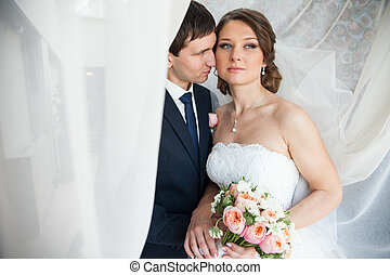 beautiful young couple in love posing under the wedding veil