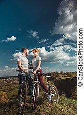 Beautiful young couple in love walking with bicycles hugging and looking at each other. The concept of joy and happiness