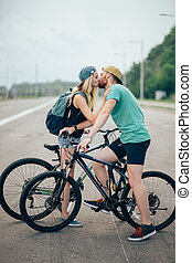 Beautiful young couple in love walking with bicycles, kissing and hugging