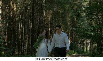 Beautiful young couple in white clothes walking in the woods.