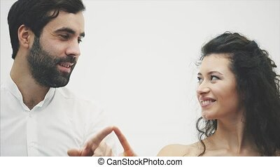 Beautiful young couple. Incredibly in love In the air, the fingers draw a heart kissing. Valentine's Day Celebration. The guy is dressed in a white shirt girl in a red dress.
