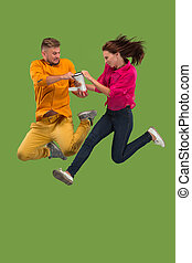 Beautiful young couple jumping with megaphone isolated over green background