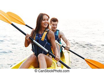 Beautiful young couple kayaking on lake together