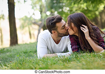 Beautiful young couple laying on grass in an urban park.