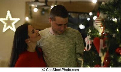 Beautiful young couple looking at Christmas tree at home.