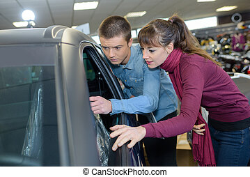 beautiful young couple looking for new car at car dealer