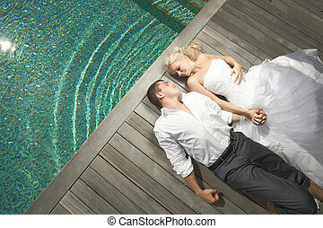 Beautiful young couple lying near pool with mind waves.