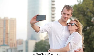 Beautiful young couple makes selfie in the street
