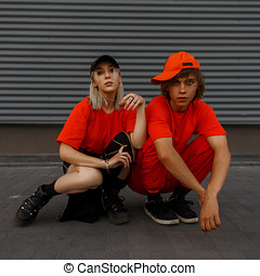 Beautiful young couple of friends of a girl and a boy with a cap in fashionable orange clothes with stylish shoes are sitting near the gray metal wall
