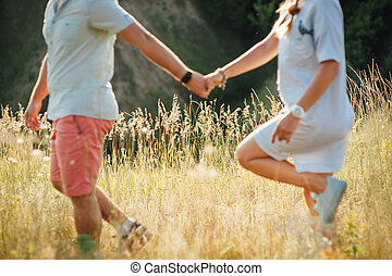 beautiful young couple on a field at sunset