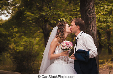 beautiful young couple posing in the park on a background of nature