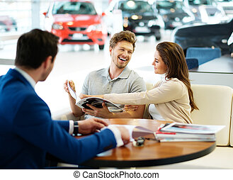 Beautiful young couple reading a booklet at the dealership...
