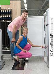 Beautiful Young Couple Shopping A Fridge In Supermarket -...