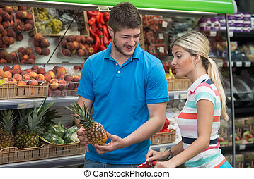 Beautiful Young Couple Shopping In A Grocery Supermarket -...