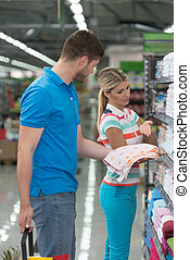 Beautiful Young Couple Shopping Trolley In Supermarket -...