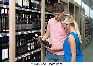 Beautiful Young Couple Shopping Vino In Supermarket -...