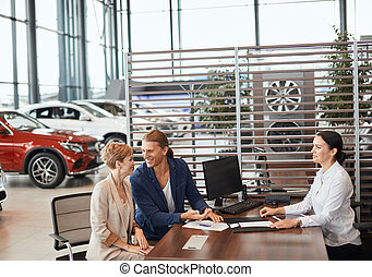 Beautiful young couple signs documents at car dealership office.