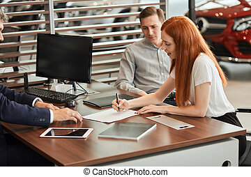 auto business, sale and people concept - happy caucasian couple buying car and Sales Rep suggests to sign a form of a Vehicle Sales Agreement at car dealership
