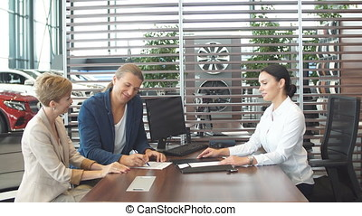 Beautiful young couple signs documents at dealership showroom.
