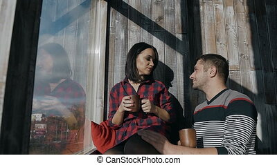 Beautiful young couple sitting around the window at home on a sunny winter day and drink hot chocolate. Christmas day and holiday