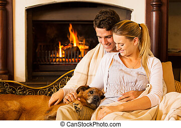 young couple sitting by fireplace with their pet dog -...