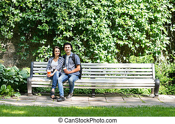 Beautiful young couple sitting on the bench with a cup of coffee in summer time