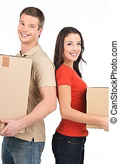 Beautiful young couple standing close to each other. man and woman smiling at camera while holding cardboard boxes