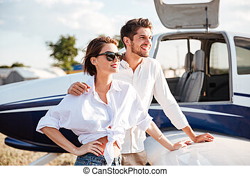 Beautiful young couple standing near small private aircraft