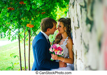Beautiful young couple standing on a stone wall background